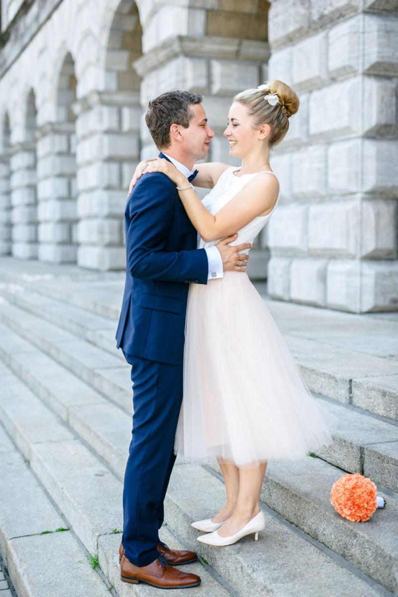 Das Brautpaar steht auf den Stufen des Standesamts und sieht sich in die Augen