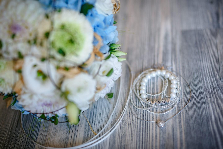 der Brautstrauß ist unscharf im Vordergrund zu sehen und ein Armband mit dem Schriftzug Braut im Fokus.