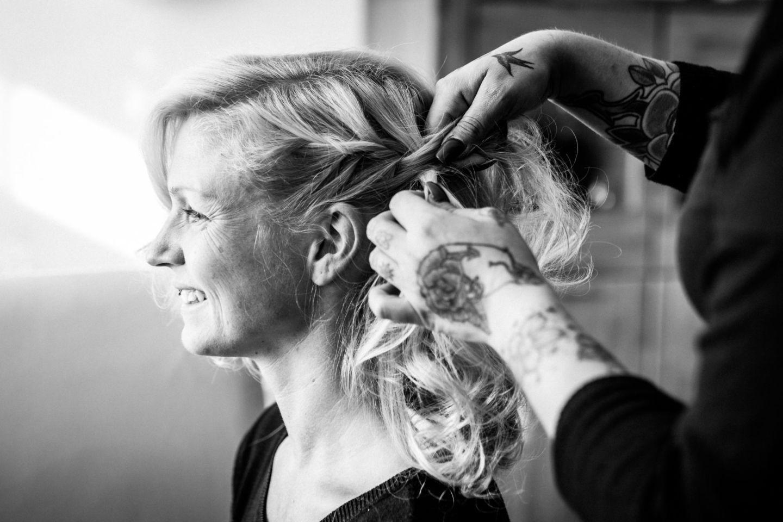 die Braut bekommt beim Fertigmachen ihre Haare geflochten