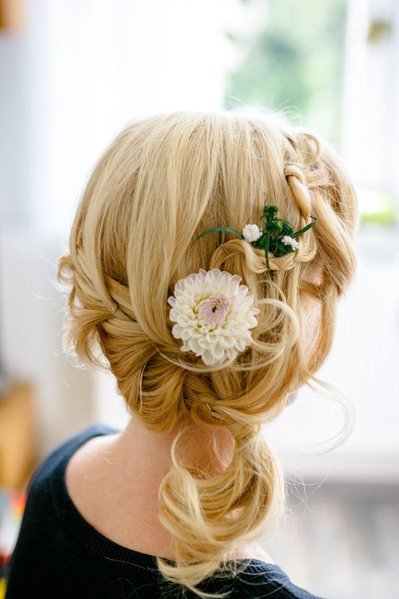 in die Frisur der Braut sind Blumen eingeflochten