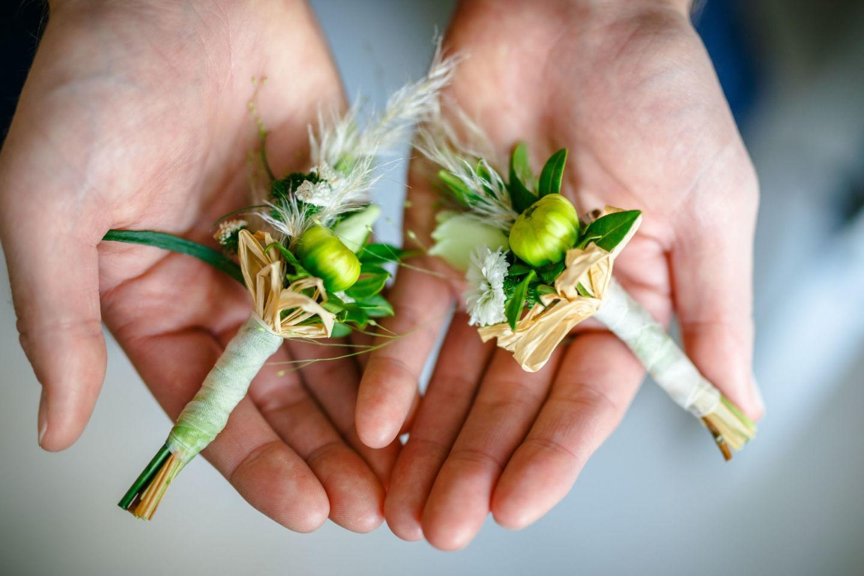 Zwei Hände halten die Ansteckblumen für Bräutigam und Trauzeugen ind ie Kamera