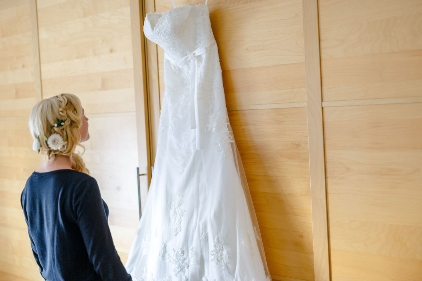 Das Brautkleid hängt am Schrank und die Braut sieht es sich sehnsuchtsvoll an