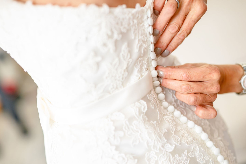zwei Hände knöpfen das Hochzeitskleid zu