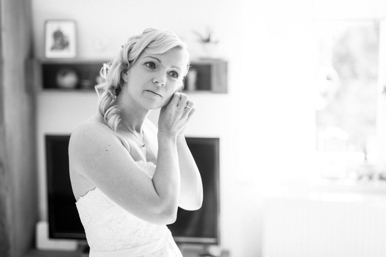 Die Braut steckt sich die Ohrringe in die Ohren