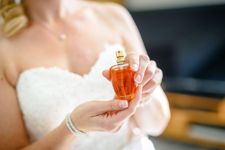 Beim Getting Ready hält die Braut ihren Parfumflakon in die Kamera
