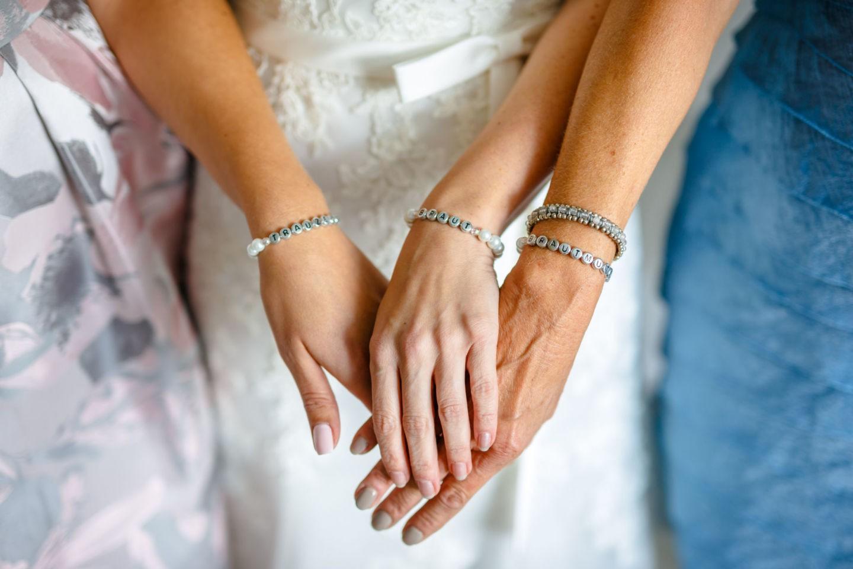dei Hände mit Armbändern Braut, Brautmutter und Trauzeugin