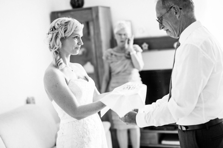 die Braut überreicht dem Brautvater ein besticktes Taschentuch als Geschenk
