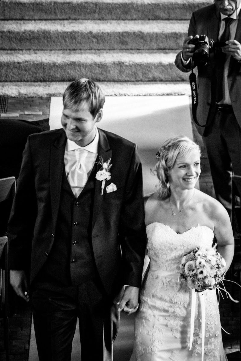 das frisch vermählte Brautpaat geht den Kirchengang entlang