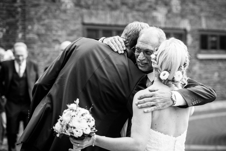 Der Brautvater schließt das Brautpaar in seine Arme