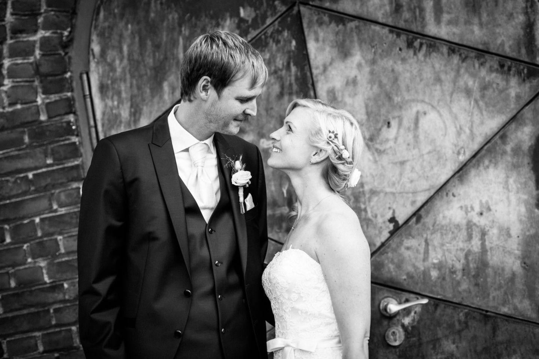 das Brautpaar sieht sich vor der Kirche verliebt in die Augen