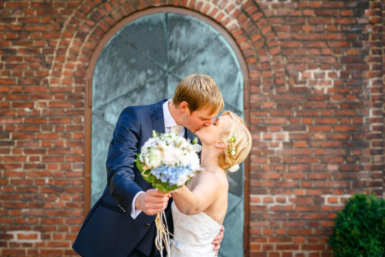 Das Brautpaar küsst sich und hält den Brautstrauß in die Kamera des Hochzeitsfotografen