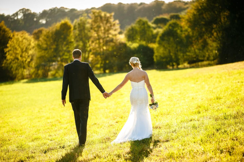 Das Brautpaar ist von hinten zu sehen wie es spazieren geht