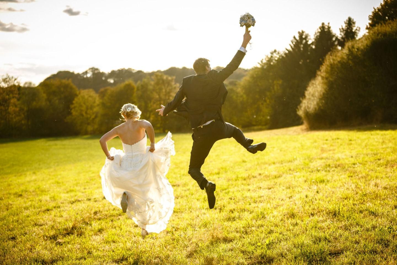 Das Brautpaar ist von hinten zu sehen und springt vergnügt in die Luft
