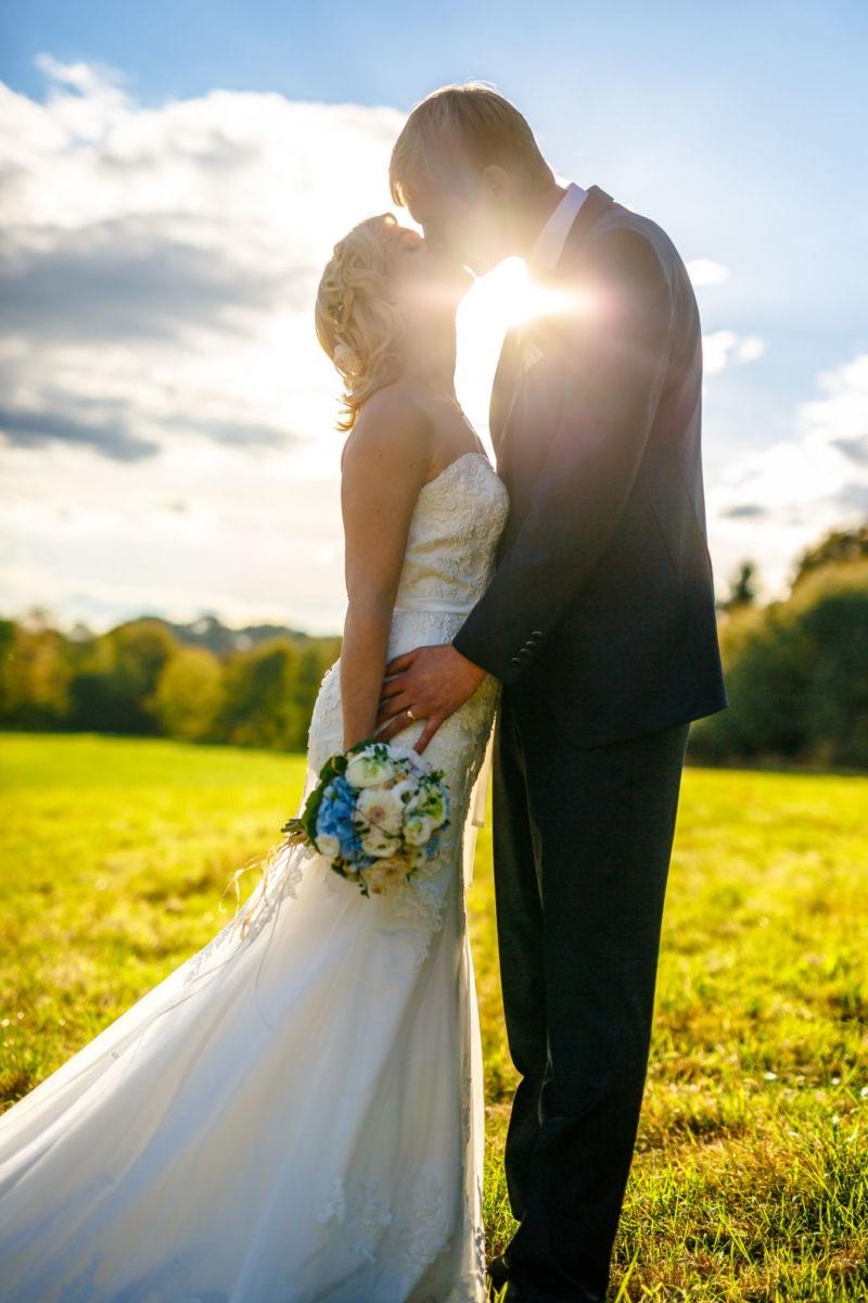 Das Brautpaar küsst sich, die Sonne strahlt durch eine kleine Lücke hindurch
