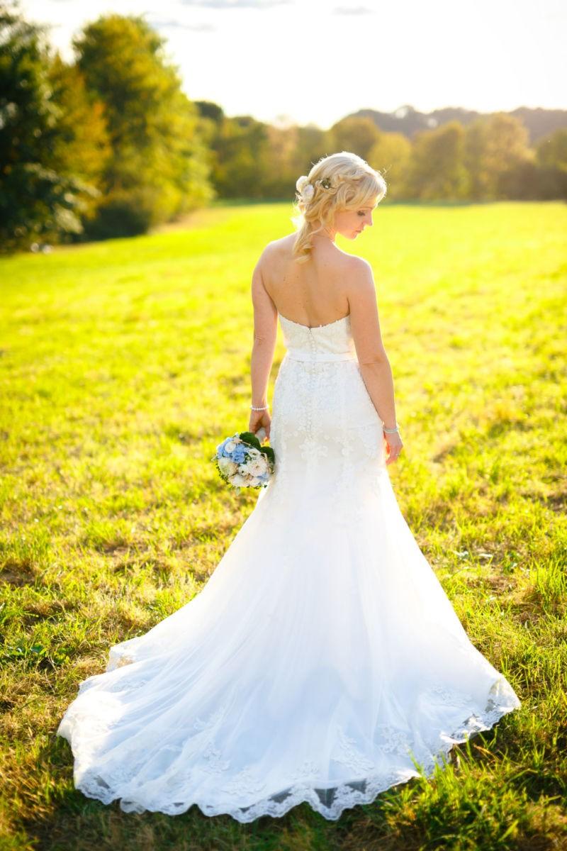 die Braut ist von hinten zu sehen wie sie über ihre Schulter guckt