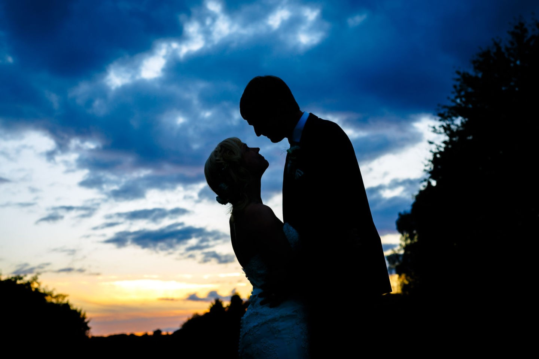 In der Abenddämmerung sind die Silhouetten von Braut und Bräutigam zu sehen
