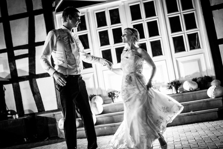 Braut und Bräutigam tanzen im dunkeln mit Licht inszeniert