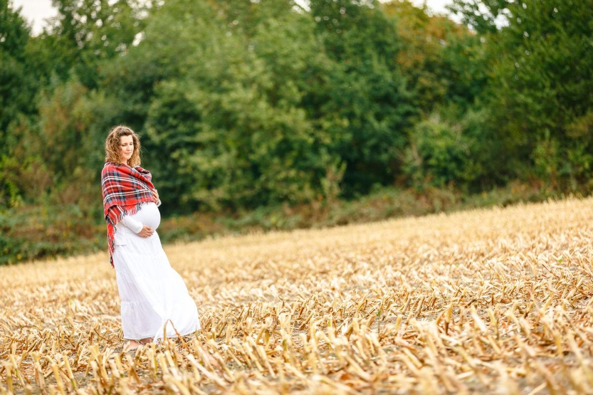 Eine Schwangere steht auf einem Feld bei ihrem Schwangerschafts Shooting