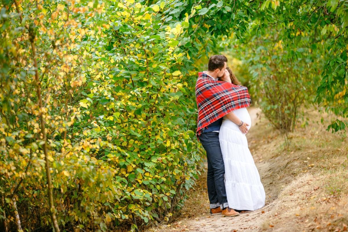 Die werdenden Eltern küssen sich bei ihrem Paarshooting