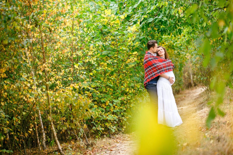 Die werdenden Eltern kuscheln sich in eine Decke und sehen sich dabei an.