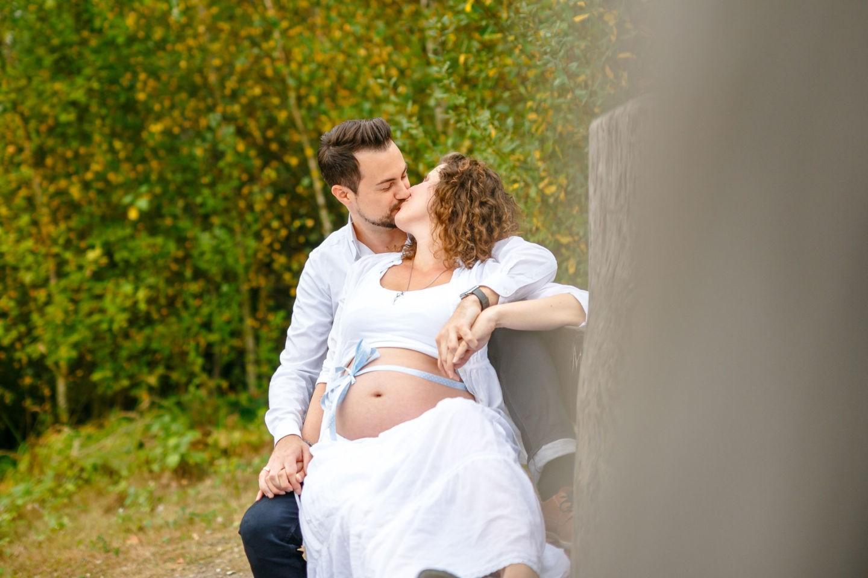 Die werdenden Eltern sitzen auf einer Bank und küssen sich. Um den schwangeren Bauch ist eine Schleife gebunden.