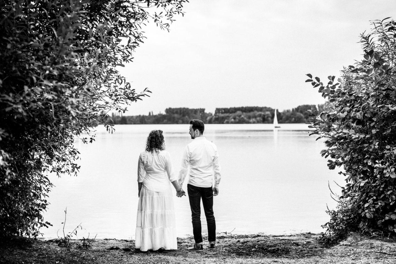 Das Paar ist von hinten zu sehen und blickt Hand in Hand auf einen See