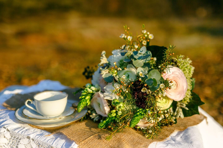 Ein großer Blumenstrauß mit vintage Geschirr auf Jute und Spitze