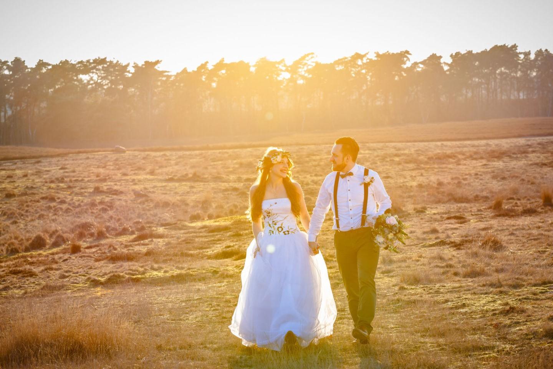das Brautpaar läuft Hand in Hand über die Heide in Haltern