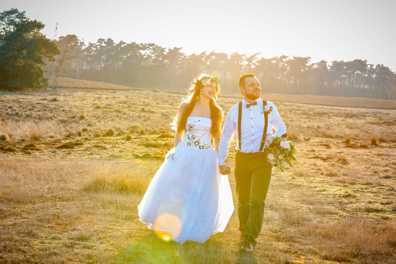 Das Brautpaar läuft Hand in Hand durch eine Heidelandschaft