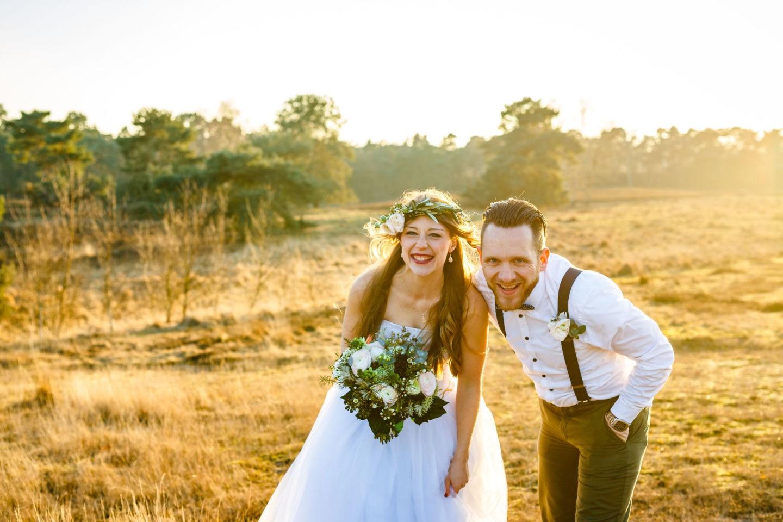 Braut und Bräutigam stehen auf einem Feld und lachen in die Kamera