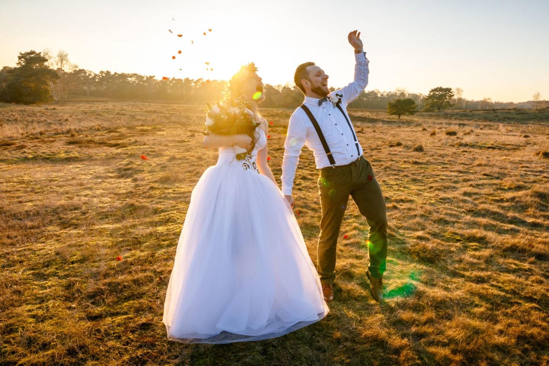 Braut und bräutigam stehen im Blütenregen