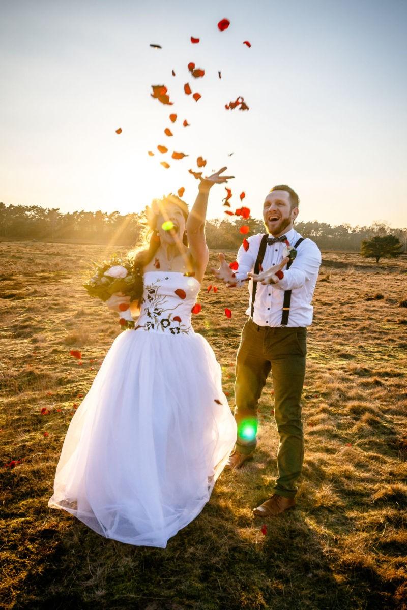 Braut und Bräutigam fangen fliegende Rosenblätter auf