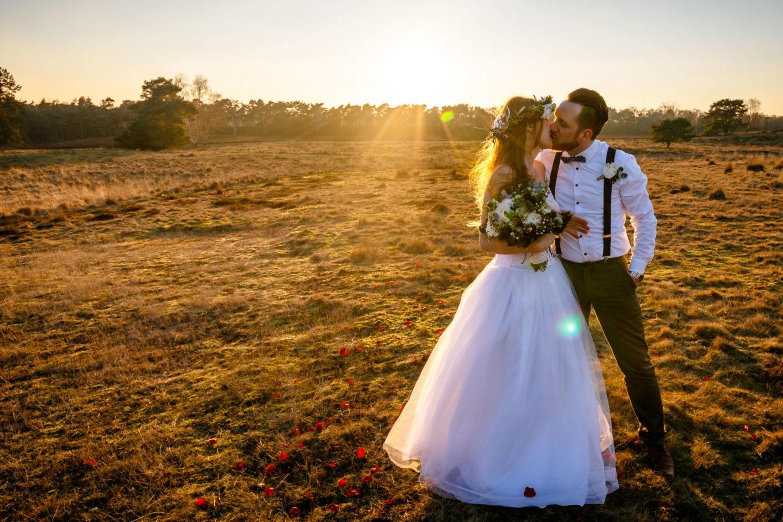 Braut und Bräutigam stehen auf der Westruper Heide in Haltern und küssen sich