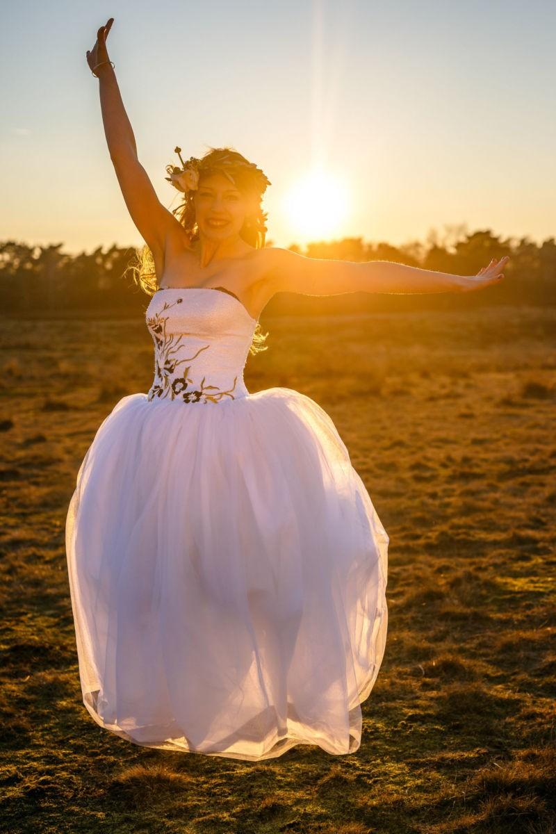 Die Braut springt lächelnd in die Luft