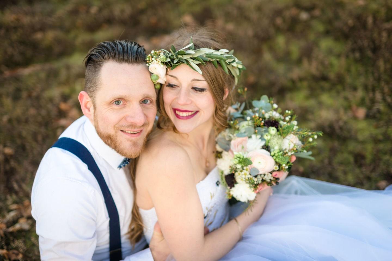 Das Brautpaar sitzt auf dem Feld und sieht glücklich aus.