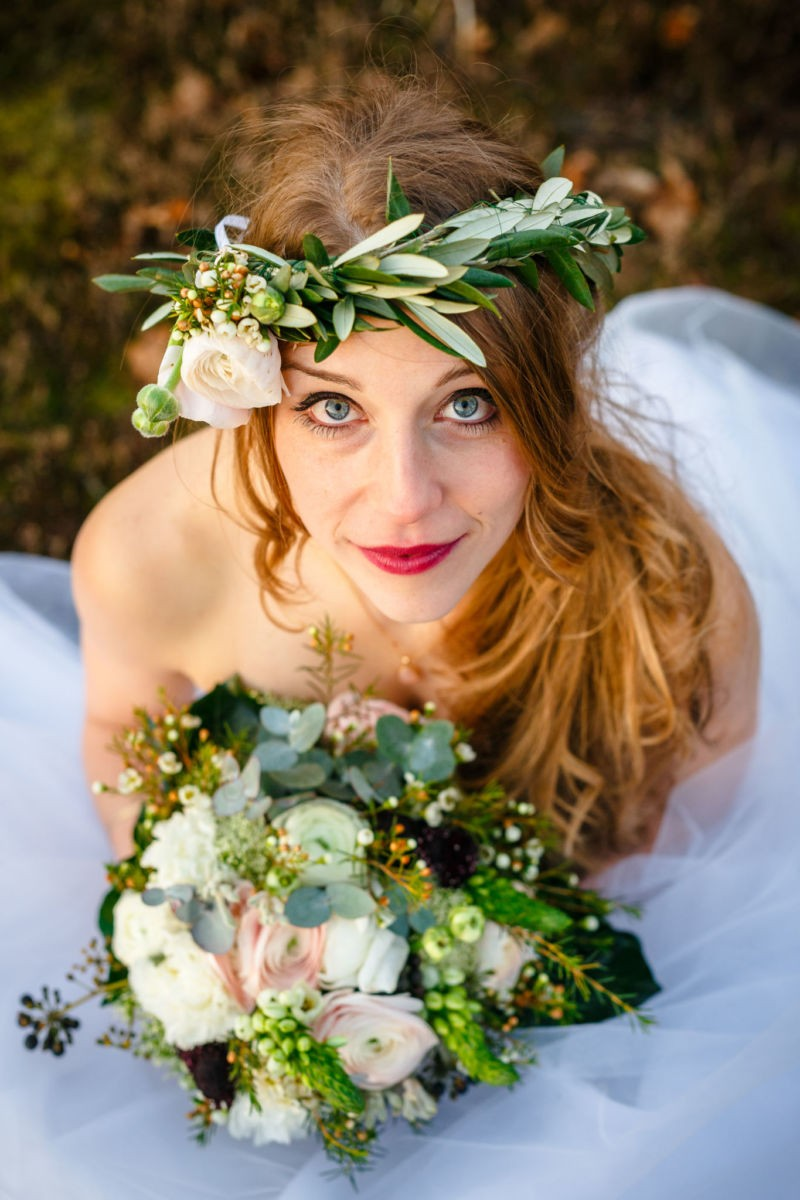 Die Braut sieht von unten nach oben in die Kamera und hält ihren Brautstrauß im Arm