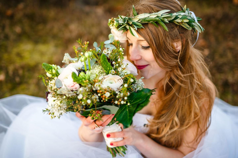 Die Braut sitzt auf der Erde und riecht an ihrem Brautstrauß