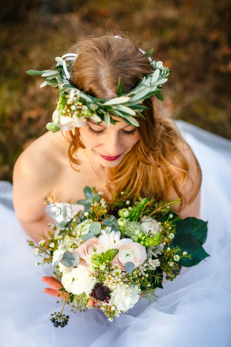 die Braut sitzt auf der Erde und schaut ihren Strauß an, Hochzeitsfotograf Haltern