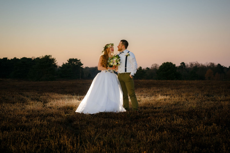 ein Hochzeitsfoto, Braut und Bräutigam stehen auf einem Feld und sehen sich an