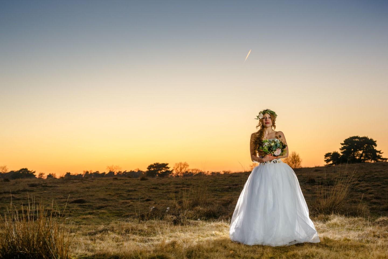 Hochzeitsbilder in Haltern, Die Braut steht mit ihrem Brautstrauß auf einem Feld