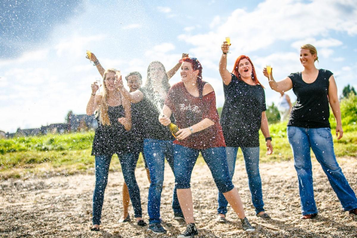 Die Junggeselling spritzt mit einer Sektflasche während die Mädels im Hintergrund der Kamera zuprosten.