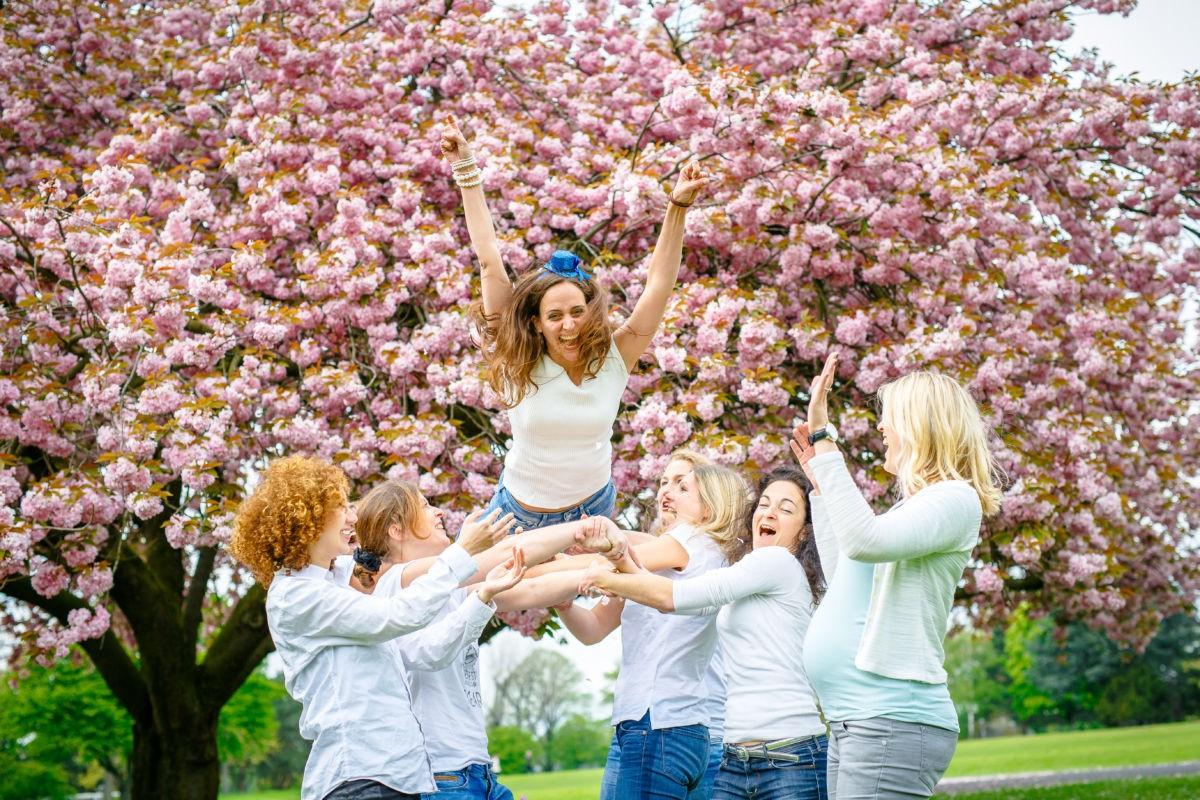Bei einem JGA Shooting treffen wri uns mit den Mädels und machen schöne Freundinnen Bilder. Hier fangen die Mädels die Braut in Spe auf. Im Hintergrund ist ein blühender Baum zu sehen.