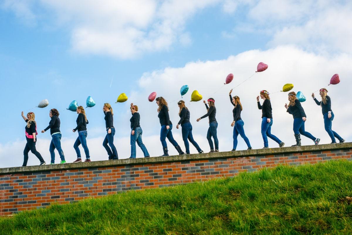 Junggesellinnenshooting in Hilden, die Mädels laufen in einer langen Reihe auf einer Mauer und haben Luftballons in den Händen.