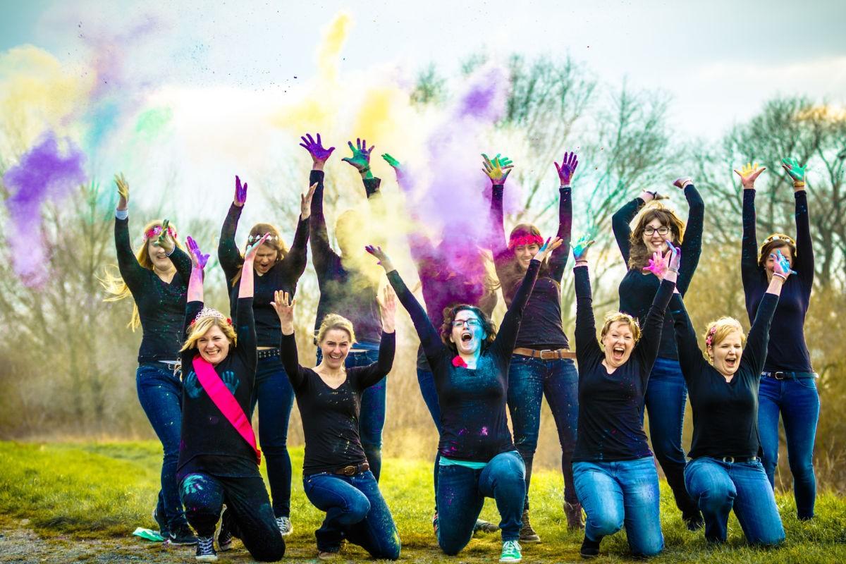 Bei diesem JGA werfen die Mädels buntes Farbpulver in die Luft und lachen in die Kamera.