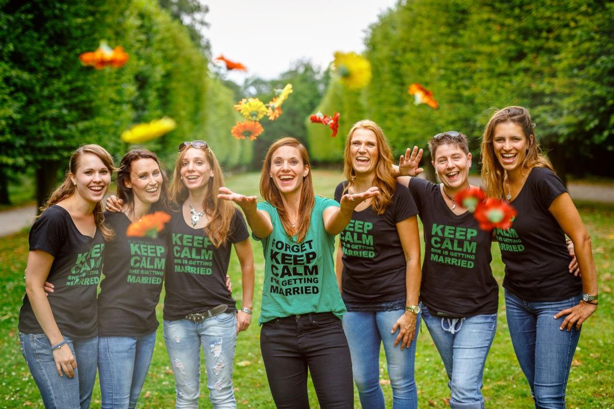 Sieben Mädels lache in die Kamera und werfen mit Blumen