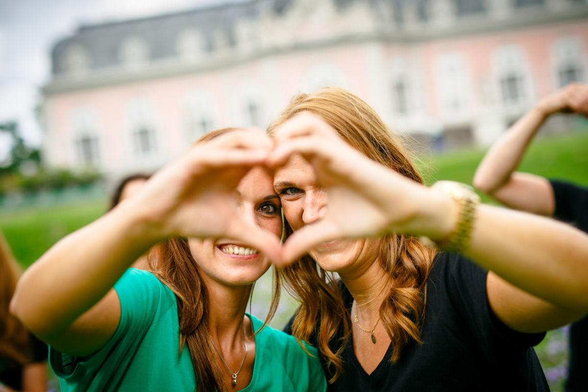 Zwei Mädchen formen ein Herz aus ihren Händen uns schauen hindurch.