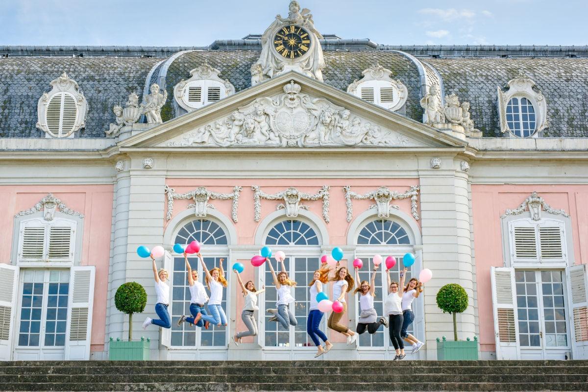 Vor Schloss Benrath in Düsseldorf springen 10 Mädels in die Luft und haben dabei Luftballons in den Händen.