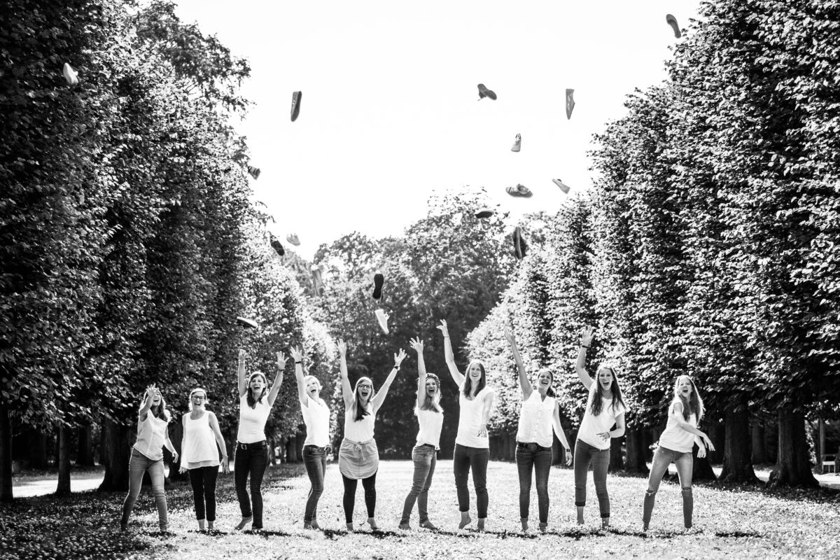 Eine Gruppe Mädchen wirft ihre Schuhe in die Luft und lacht dabei herzhaft.