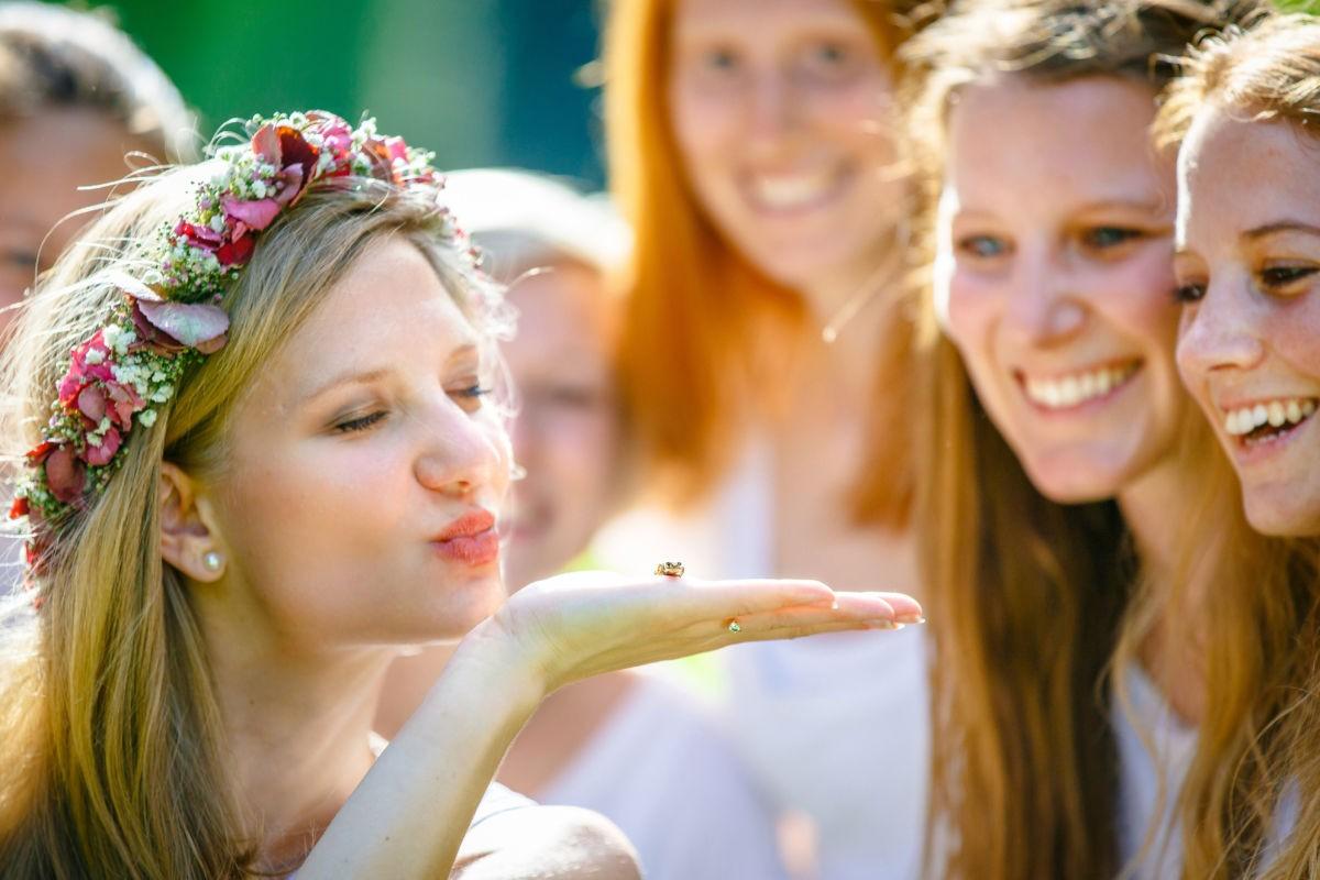 im Vordergrund ist die Junggesellin zu sehen. Sie trägt eine Blumenkranz und küsst einen kleinen Frosch, der auf ihrer Hand sitzt.