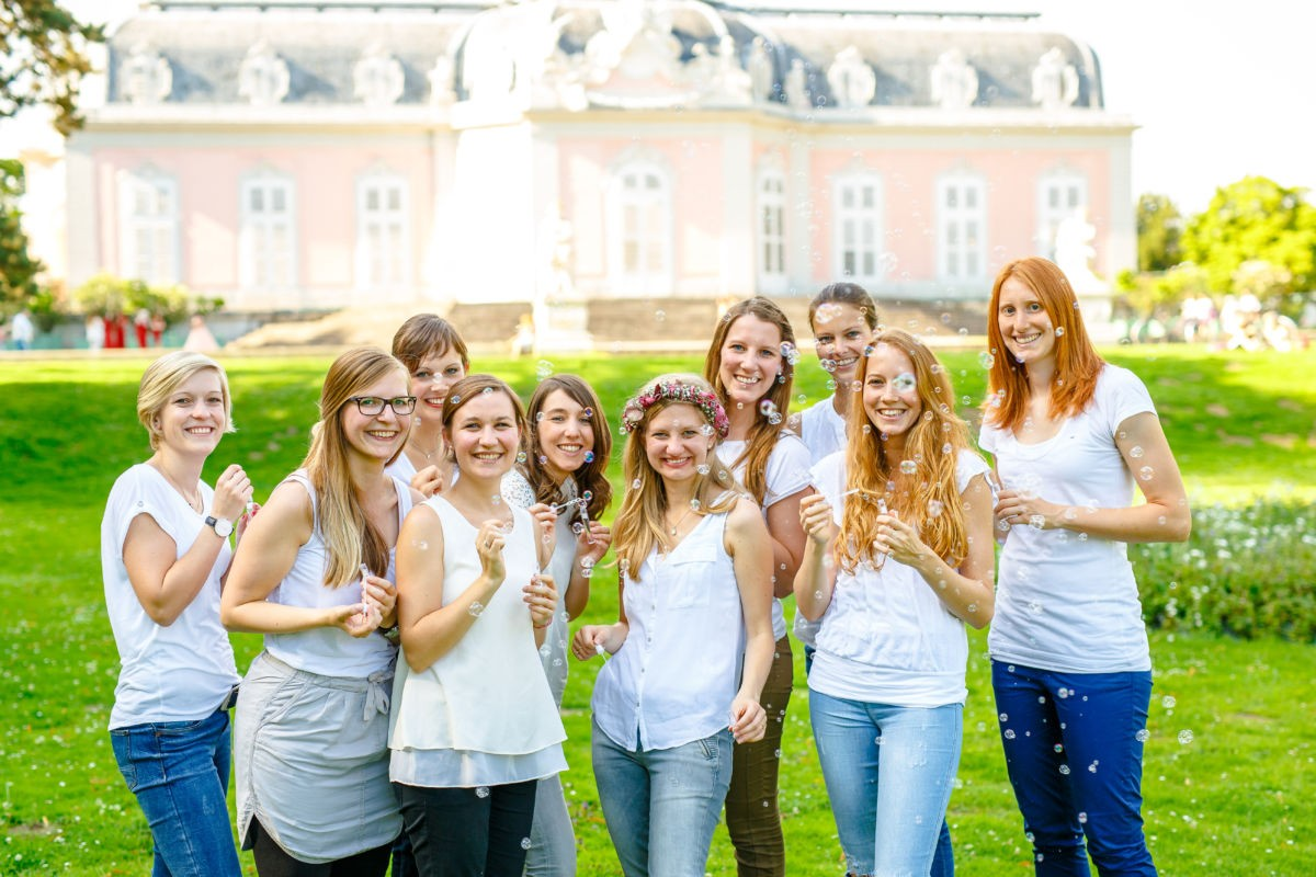 Eine Gruppe Mädchen steht vor dem Schloss Benrath in Düsseldorf und pustet Seifenblasen.